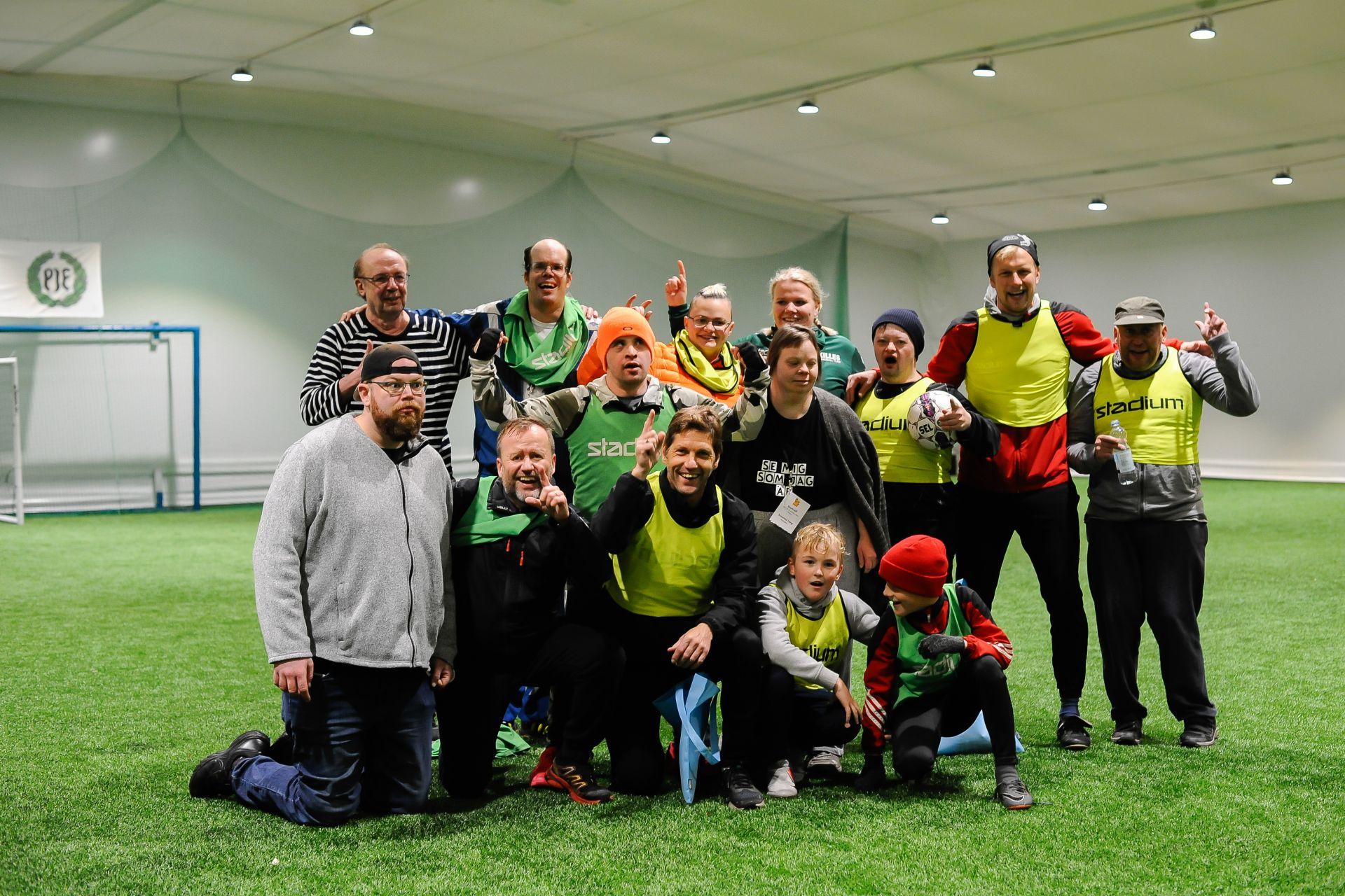 En gruppbild på glada personer vid en inomhusfotbollshall.