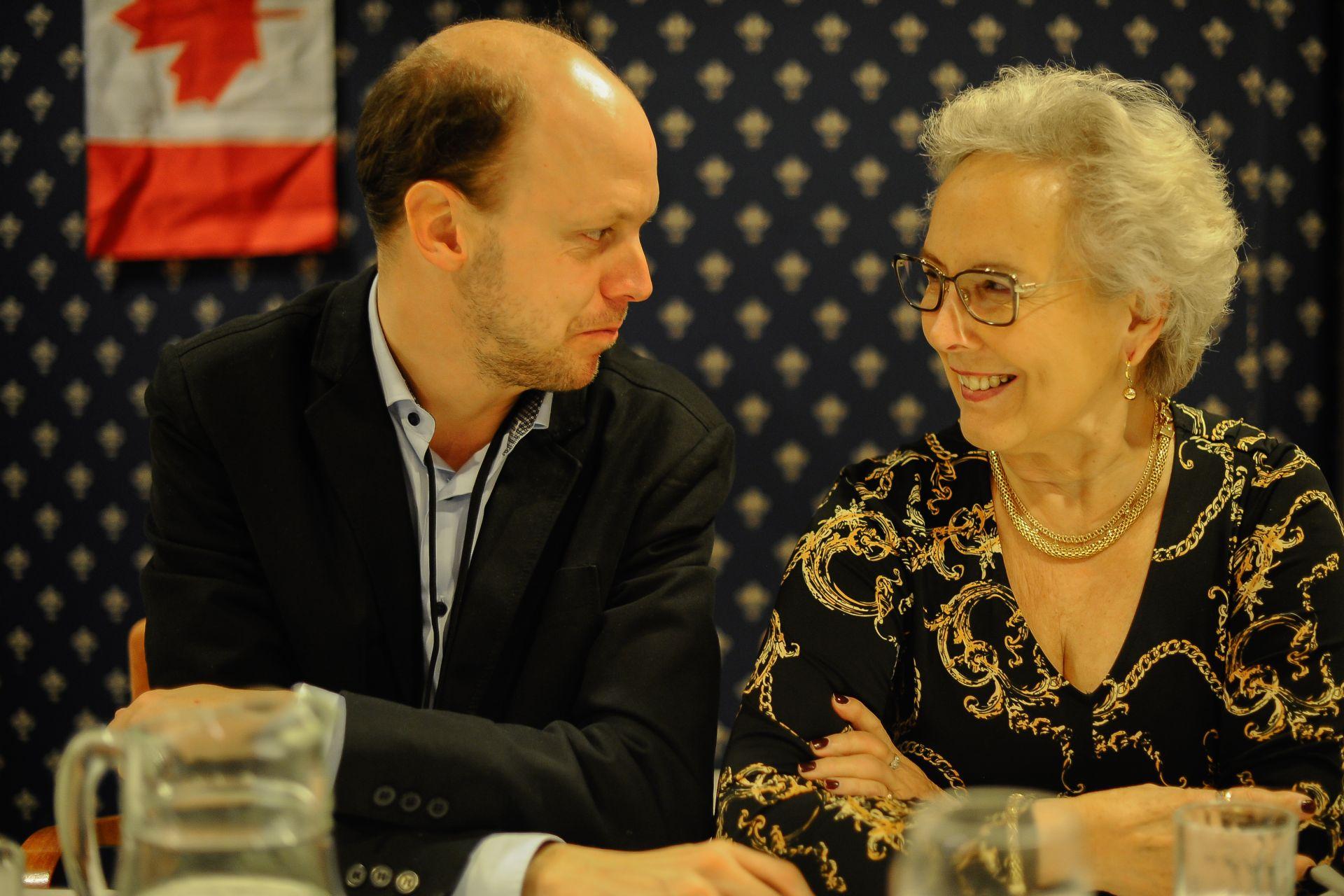 Två personer sitte vid ett festbord och talar